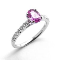 A Solitaire Ring Set with a Pink Sapphire and Diamond Set Shoulders in Platinum
